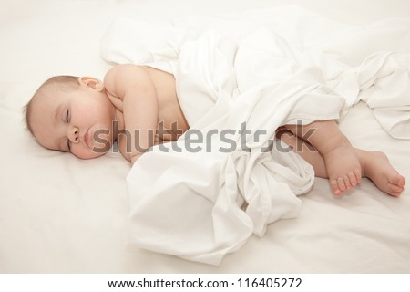 Newborn baby sleeping together with his mother in the bed on white sheets. Mothers hand holding baby. Selective focus on babys head - stock photo