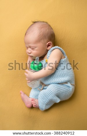 Newborn baby sleeping with a bottle, in blue knit outfit, on blanket. Bottle feeding concept. - stock photo