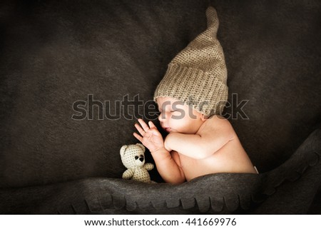 newborn baby sleeping  with a toy next to the  knitted teddy bear