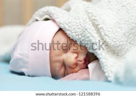 newborn baby sleeps under blanket