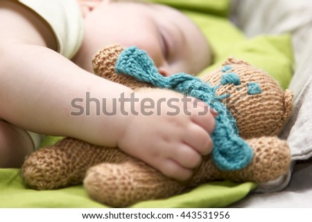 newborn baby sleeps with a toy teddy bear - stock photo