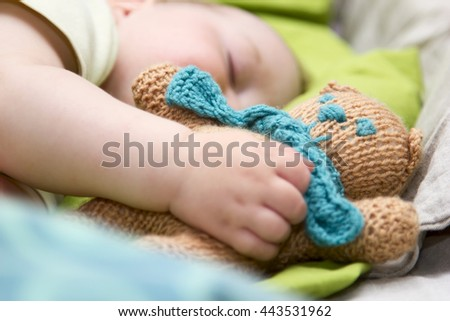 newborn baby sleeps with a toy teddy bear white - stock photo
