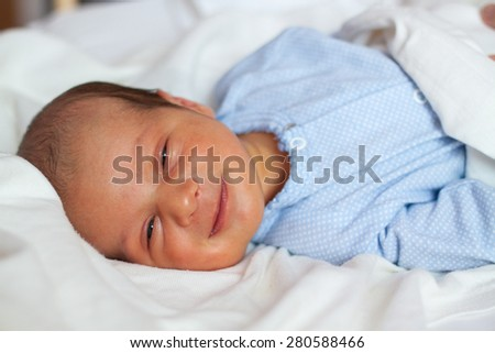 Newborn baby smiling in the bed