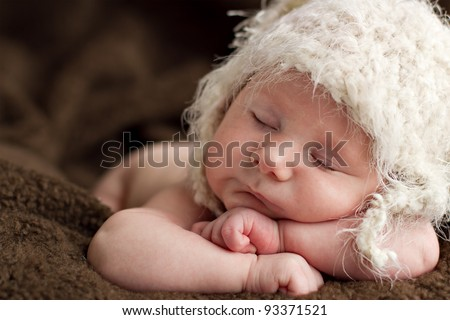 Newborn baby 6 weeks old sleeping on soft brown fluffy rug with funky woollen hat