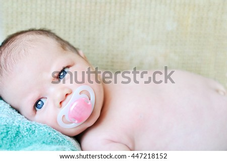 newborn baby with dummy on the bed - stock photo