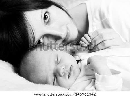 Newborn baby with happy mother, black and white