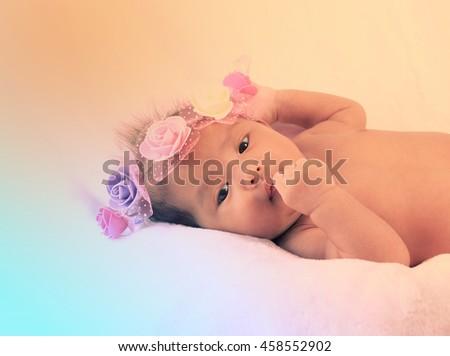Newborn baby with headband on the head lying on blanket.  - stock photo