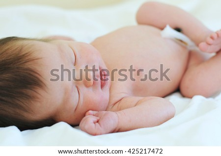 Newborn baby with umbilical cord sleeping - first birth day