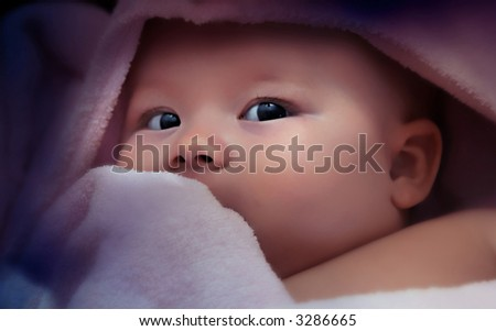Newborn child laying in violet towel