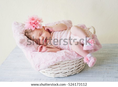 Newborn girl in pink clothes sleeping in decorative basket