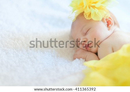 Newborn girl is sleeping in yellow skirt with hat - stock photo