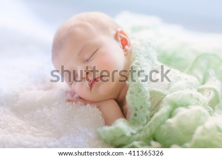 Newborn girl is sleeping under green cover. Sleeping time. - stock photo
