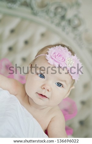 newborn girl on a bed with a beautiful headboard in the background