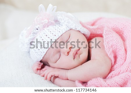 newborn girl sleeps under a knitted pink cape