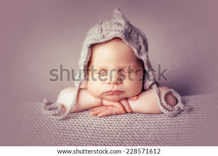 Newborn in hat on the blankets folded handles - stock photo