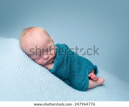 Newborn infant baby asleep posed on a blanket, in a knit wrap - stock photo