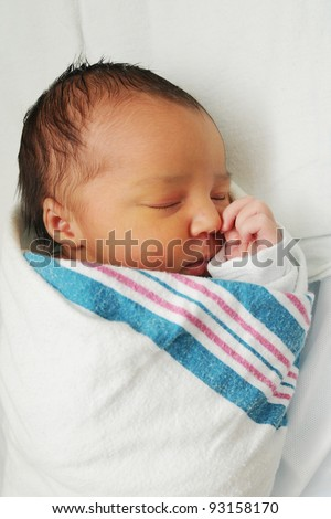 Newborn Infant Baby sleeping wrapped in blanket - stock photo