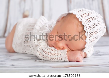 Newborn infant wearing nice homemade cap sleeping  - stock photo