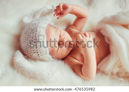newborn lying on blanket in a white hat rabbit