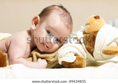 newborn lying on the cute toy bear - stock photo