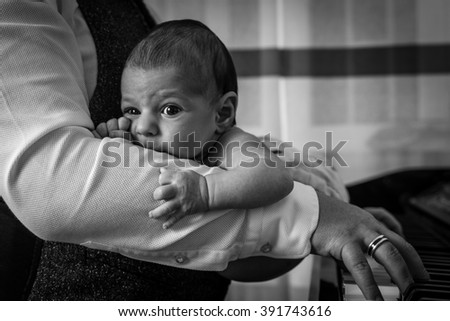 Newborn on his dad's arms while he's playing a piano - stock photo