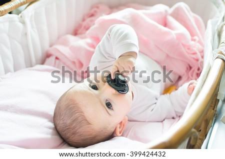 newborn pink cradle hold black pacifier hand - stock photo