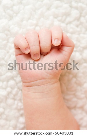 newborn's baby hand in a fist on a blanket - stock photo
