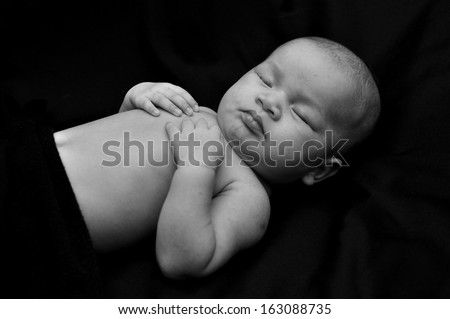 Newborn sleep in black background