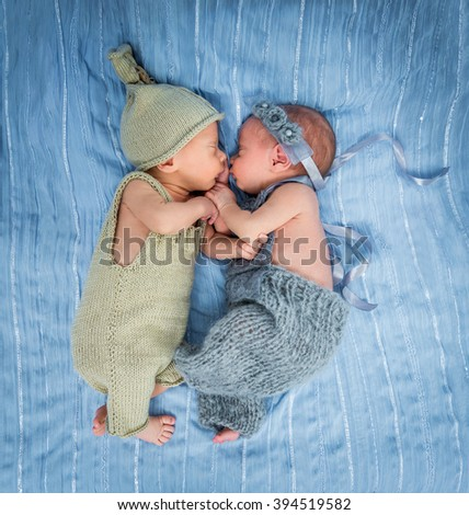 newborn twins - a boy and a girl sleeping on a blue blanket - stock photo
