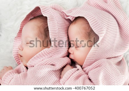 Newborn twins sisters sleeping on white fur, hugging each other and wearing cute pink sweaters - stock photo