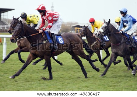 NEWBURY, BERKS- 26 MAR:  Jockeys jostle for position over hurdles in the fifth race at Newbury Racecourse, Newbury, Berks on 26 March 2010