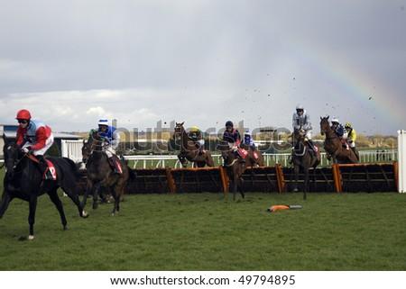 NEWBURY, BERKS - MAR 27: Jockeys take their mounts over hurdles in the 5th race at Newbury Racecourse, UK, March 27, 2010 in Newbury, Berks - stock photo