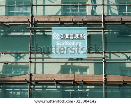 Newbury, Northbrook Street, Berkshire, England - October 10, 2015: Contractor sign on scaffolding carrying out renovation works over retail units - stock photo