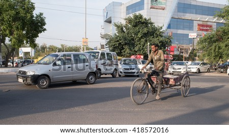 Newdelhi, India - May 06, 2016: Typical volume traffic scene in intersection in Newdelhi. Auto rickshaws and Bus Rapid Transport (BRT) buses provide public transportation. - stock photo