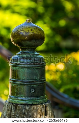 Newel post and ball in green surrounding - stock photo