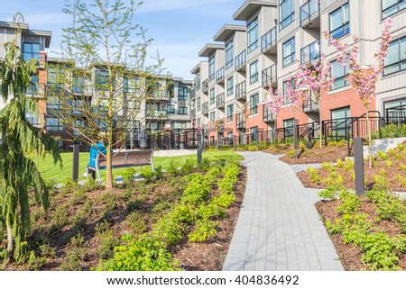 Newly built condos with nicely trimmed and designed front yard in a residential neighborhood in Canada. A man enjoying sunshine sitting on the bench. - stock photo