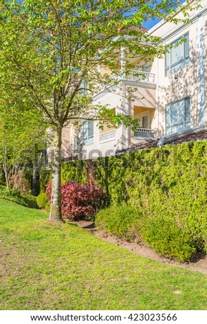 Newly built condos with nicely trimmed and designed front yard in a residential neighborhood in Canada. Side view of the complex. - stock photo