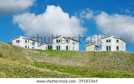 Newly built houses under the blue sky with huge white clouds. - stock photo