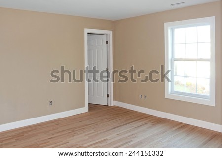 Newly constructed house interior room with unfinished wood floors window and closet door.  Electrical connections are partially unfinished. - stock photo