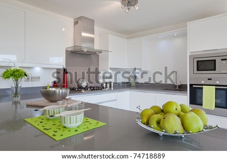 Newly fitted modern kitchen with built in appliances, utensils and basket of fruit - stock photo