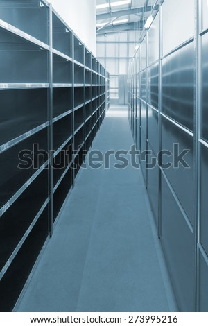 Newly installed empty warehouse storage shelves and racks in a generic warehouse rendered in blue tint - stock photo