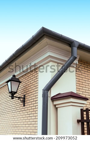 Newly installed modern rain gutter and drainpipe - stock photo