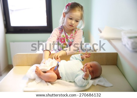 Newly made sister with her newborn brother in hospital maternity ward just before leaving for home.  - stock photo