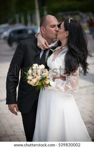 Newly married adult couple kissing on the street
