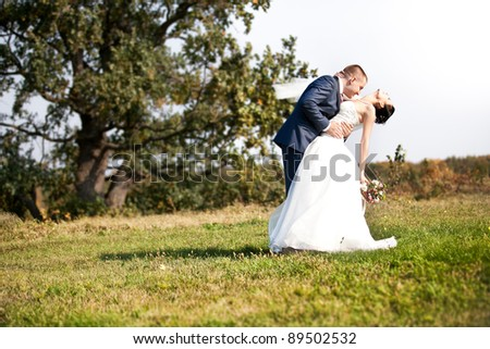 newly married couple dancing and hugging outdoor on lawn - stock photo