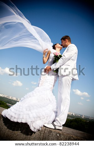 newly married couple kissing.wind lifting long white bridal veil - stock photo