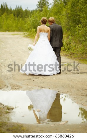 Newly-married couple walks on rural road - stock photo