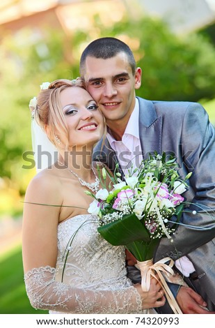 Newly-married couple with a bouquet of colours in park - stock photo