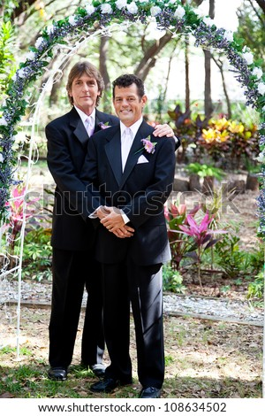 Newly married gay couple posing for a portrait under the wedding arch. - stock photo