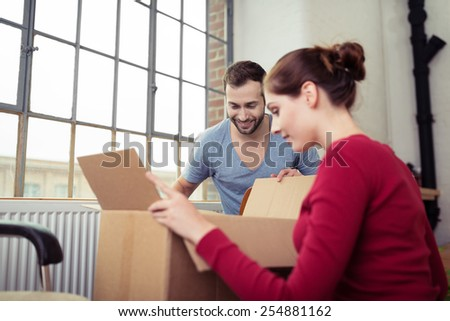 Newly Married White Couple Opening Cardboard Boxes at their New Home. - stock photo